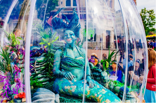 Mermaid art show inside a dome with people take photos around her