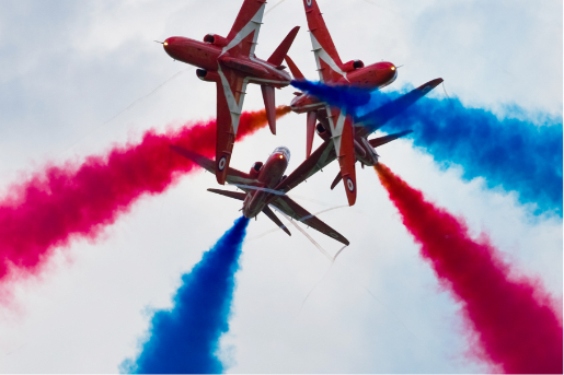 Red arrows doing a tight maneuver with red and blue smoke at the air show