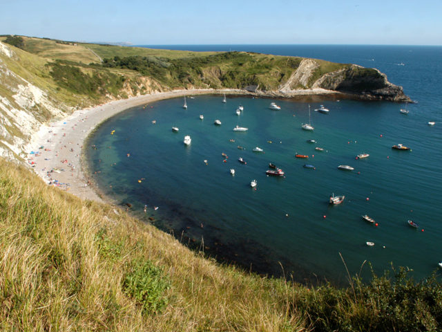 Boats moored up in Lulworth cove during the summer