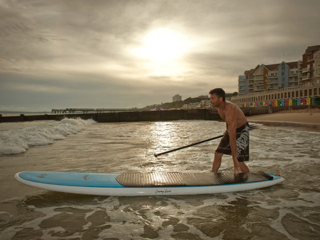 Man pushes his paddle board into the sea