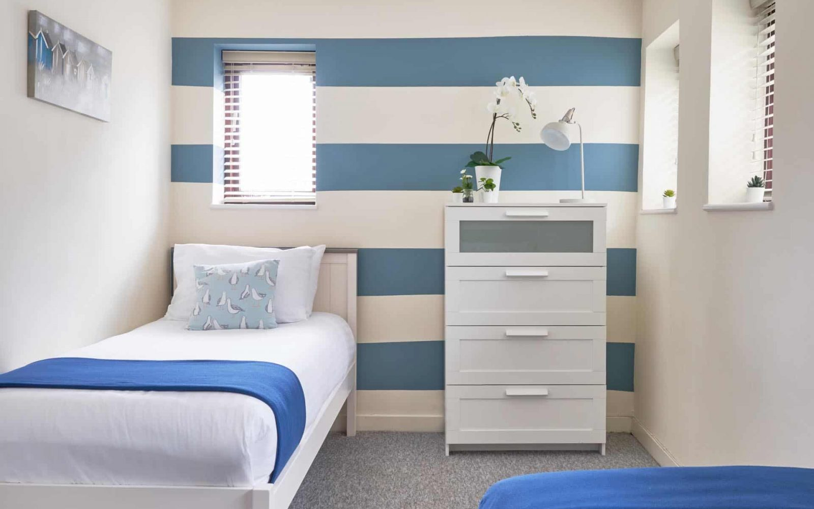 Single bed with draws and blue and white colours throughout the room
