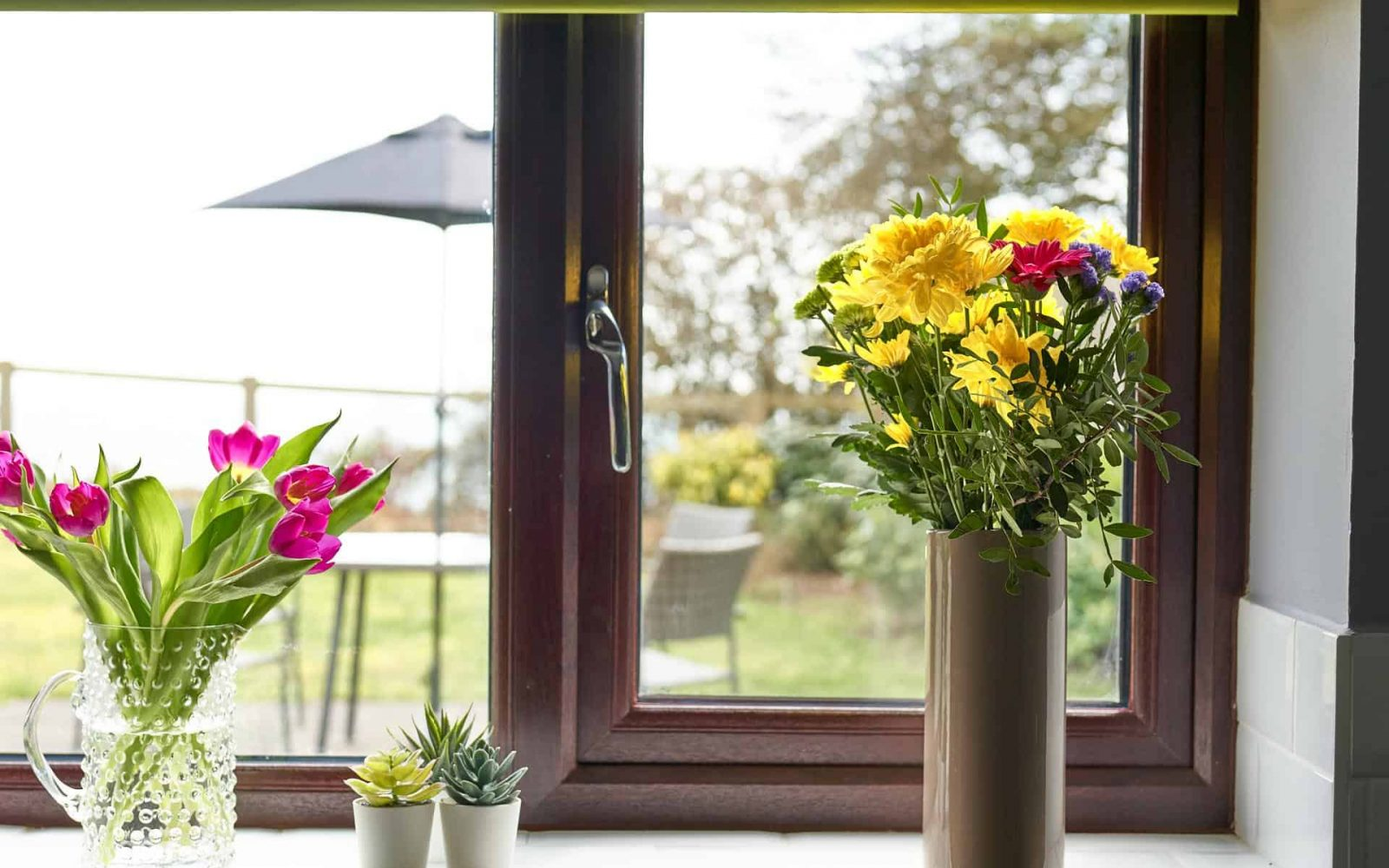 Cute and colourful flowers sat on the window sill with views of the garden