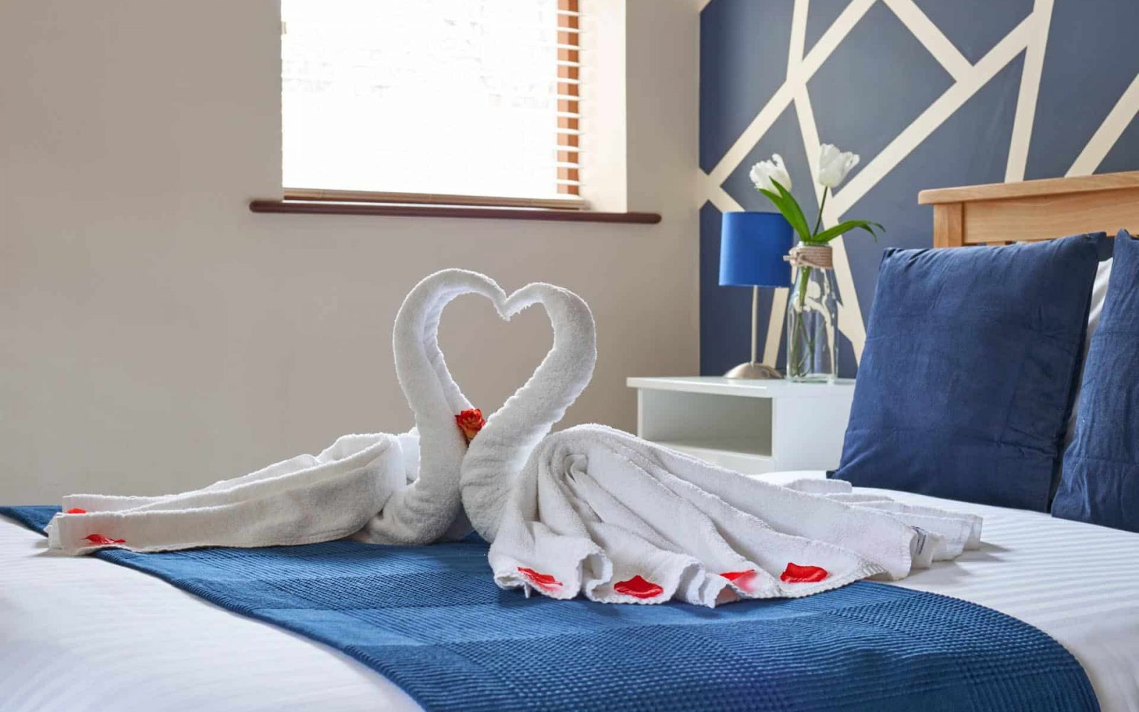 Two towels folded to make a swans and a heart shape on the bed